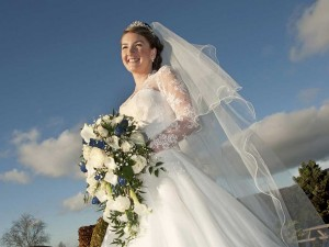 Woman in a wedding dress in front of a blue sky